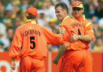 ZIMBABWE'S JOHNSON IS CONGRATULATED BY TEAM MATES AFTER BOWLING OUT CRONJE.