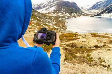 Tourist taking photo by Djupvatnet lake, Norway