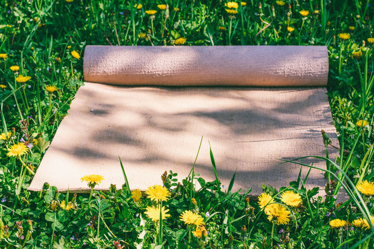 Yoga mat on a green meadow on a spring sunny day, selective focus