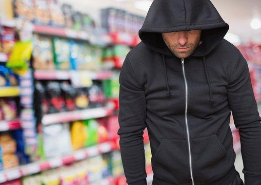 Criminal in hood in shop store