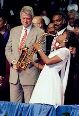 U.S. President Bill Clinton listens as Angelica Christie plays the saxophone during his visit to Orl..