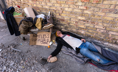 Drunk homeless man sleeping on the cardboards. Сart with his stuff is near with him.