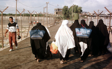 Palestinian women carry their parcels early October 13 morning as they head back through a wire encl..