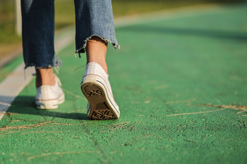 woman Sneaker white and jeans walking on the road green color with sunset light
