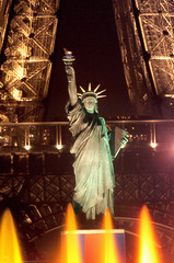 Paris' Statue of Liberty, framed by the Eiffel Tower (background), is illuminated behind colored fou..