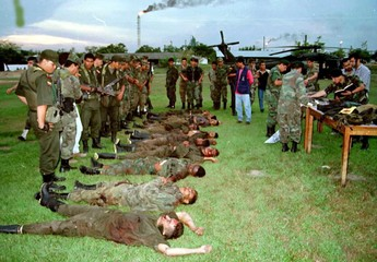 COLOMBIAN SOLDIERS LOOK AT BODIES OF GUERRILLAS.