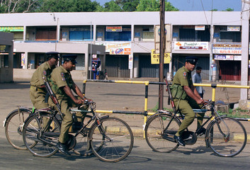 SRILANKAN POLICEMEN ON BICYCLES RIDE PAST CLOSED SHOP IN VAVUNIYA.