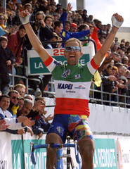 Italian cyclist Andrea Tafi raises his arms as he crosses the finish line to win the 97th edition of..