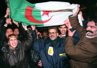 """Demonstrators hold high an Algerian flag as the shout slogans as a """"Day for Algeria"""" march starts, N.."""