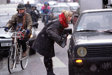 A Parisian commuter tries to get a ride from a passing car as others peddle to work on bicycles duri..
