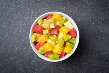 Colorful fruit salad on gray stone table. Food background