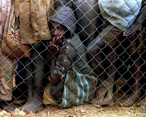 A little Hutu boy waits for his food rations June 23 along with thousands of others living in the sp..