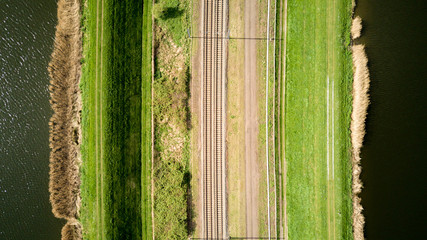 Vertical drone view of train tracks bordered by reservoirs.