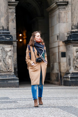 Hipster style girl on background of the old city of Dresden. A woman wearing warm coat, knitted scarf and photo camera