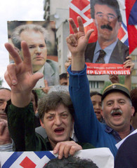 Serbs from Montenegro make a Serbian Orthodox three finger sign April 22 as they join a meeting of S..