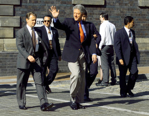 President Clinton, surrounded by his security officers, walks from his hotel to the International Co..