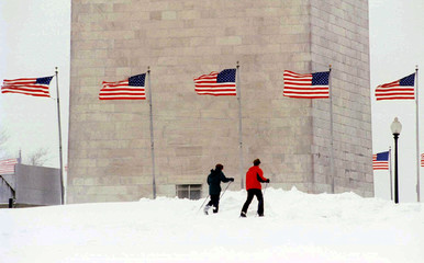 Two men ski past the Washington Monument January 12, as a new storm front hit the East Coast. The ca..
