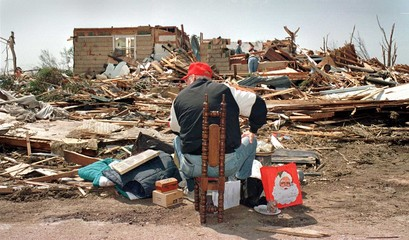 TORNADO VICTIM WATCHES BELONGINGS WHILE FAMILY SEARCHES HOUSE IN SPENCER.