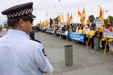 POLICE KEEP WATCH OVER PROTESTERS OUTSIDE PARLIAMENT HOUSE IN CANBERRA.