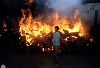 A Hindu relative stands front of a mass funeral pyre for 15 Hindus after it was set alight outside t..