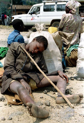 An exhausted Rwandan boy rests near a roadside clinic in Mukingo August 3 after trecking home barefo..