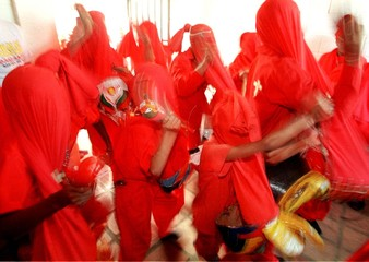 Venezuelan men and children dressed as devils with red hoods dance vibrantly inside a cemetery to bl..