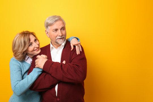 Happy senior couple on color background