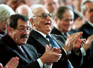 German writer Guenter Grass (L) applauds sitting next to his friend and Turkish writer Yasar Kemal (..