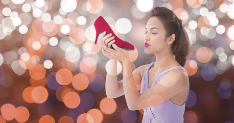 Young woman kissing new footwear over bokeh