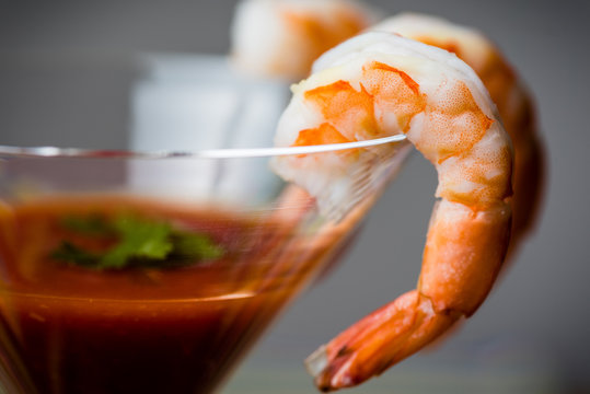 Shrimp cocktail with sauce served in a martini glass and garnished with parsley.