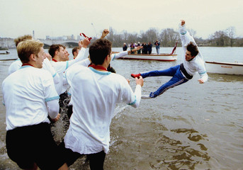The Cambridge team celebrate by throwing their cox Kevin Whyman into the river after their victory o..