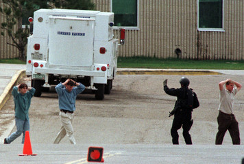 Columbine High School students are led from the building with an escort by a member of a SWAT team i..