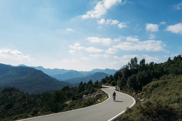 a fit young male cyclist riding on a windy spainiush mountain road through rocks and and very grren trees, soft white puffy clouds above and gently blue colored sky and hazed mountains.