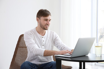 Handsome young man working with laptop at home