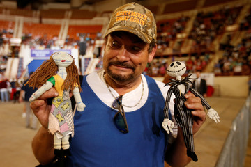 DeHaven poses for a photo with his voodoo dolls depicting Nancy Pelosi and Chuck Schumer before a U.S. President Donald Trump rally in Harrisburg