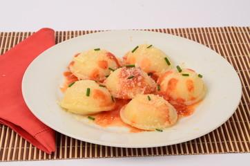 Sorrentinos, raviolones con salsa y tenedor