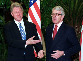 US President Bill Clinton (L) shares a laugh with British Prime Minister John Major (R) prior to a b..