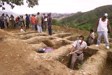 Cemetery workers dig graves for flood victims in Caracas December 19. Eighty nine people have been b..