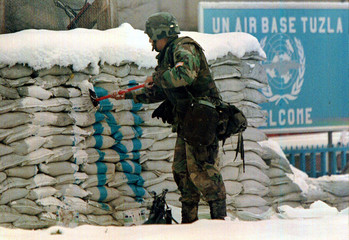 US Army specialist Efren Torres from Azusa, CA paints over a United Nations sign at a UN post outsid..