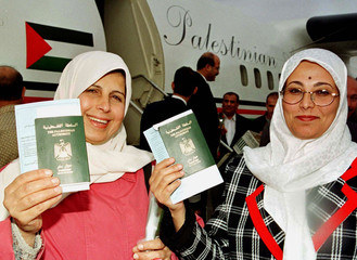 Palestinians citizens hold their passports upon their arrival by the first Palestinian commercial fl..