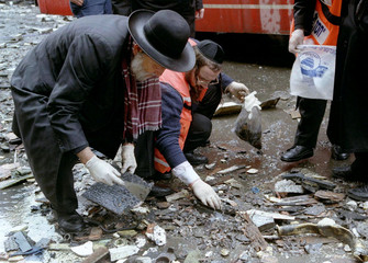 Ultra-religious Jews search for bodies pieces of victims in the wreckage that litters the street whe..
