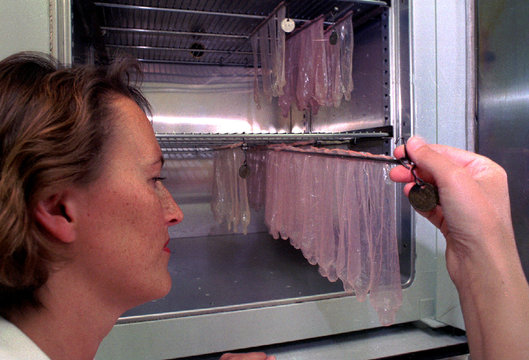 Dutch worker Ineke Zijderveld takes a look in the condom oven where condoms are tested for safety in..