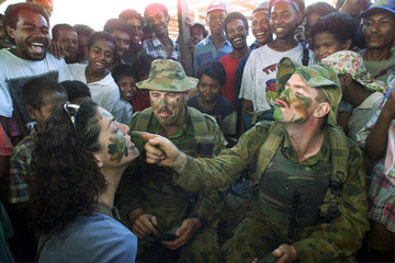AUSTRALIAN SOLDIERS PAINT FACES DURING THE RE-OPENING OF DILI MARKET.