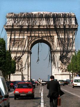 A businessman walks near Paris' Arc de Triomphe which is draped in black to protest plans to cut Eur..