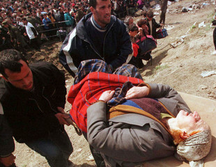 Local relief workers carry a sick Kosovo refugee woman up a hill out of the refugee camp at Blace Ap..