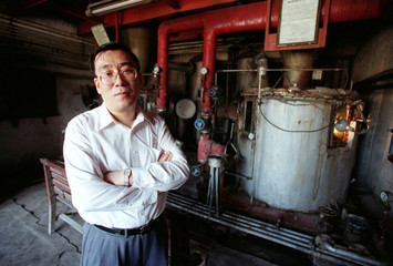 """Chinese entrepreneur Jiang Enhong poses in front of an old still at the 300-year-old """"Old Dragon's M.."""