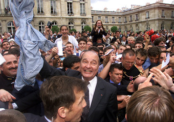 French President Jacques Chirac (C) holds a lost blue jean jacket as he walks among guests during th..