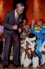 African National Congress President Nelson Mandela dances alongside a traditionally dressed child du..