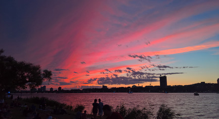 Silhouetted couple and other onlookers admiring a brilliant colorful sunset over the Charles River on the Esplanade in Boston on July 3rd, 2016