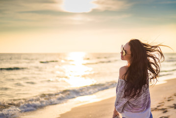 Brunette girl on the background of the sea sunset
